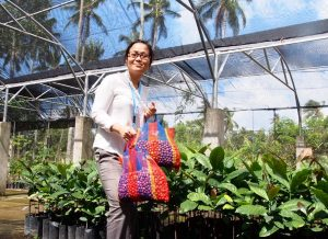 A woman smiling at the camera, holding a bag of coffee beans in front of plants in a greenhouse.